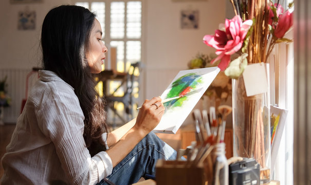 Cropped shot view of Woman painter sitting on the floor in front of the canvas and drawing. Artist studio interior. Drawing supplies, oil paints, artist brushes, canvas, frame.
