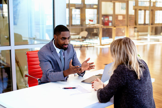 Portrait of a young man in business suit with female client or business woman  explaining contract in office meeting