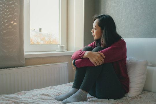 Woman is sitting on the bed looking out to the windows and thinking or missing of someone.