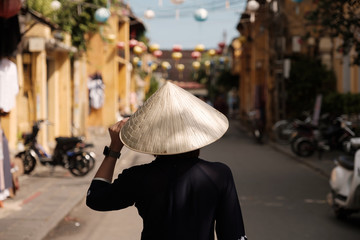 Beautiful girl wearing vietnam hat or Non La and sightseeing at Heritage village in Hoi An city in Vietnam.