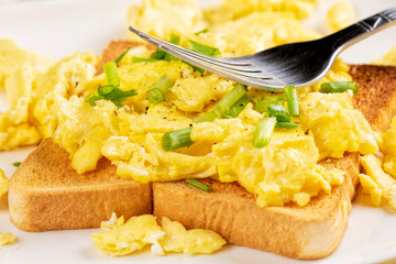 Delicious breakfast of scrambled eggs and toast with copy space