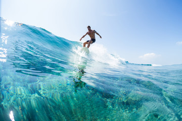 Surfer rides the glassy ocean wave in tropics