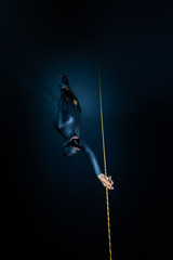 Wall Mural - Woman freediver descends along the rope into the depth