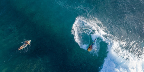 Wall Mural - Surfers in the ocean, top to down aerial shot