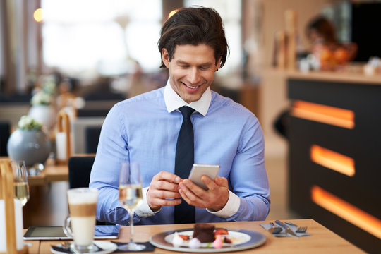 Businessman with smartphone at lunch in cafe