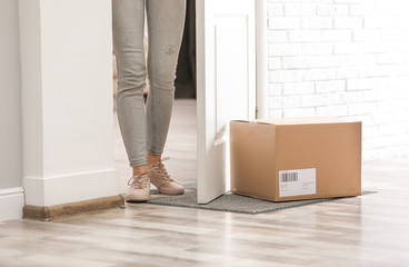 Woman in doorway and parcel on rug, closeup. Delivery service