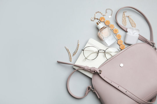 Stylish woman's bag with accessories on light grey background, flat lay. Space for text