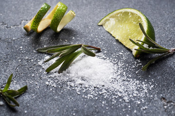 Slices of fresh lime, salt and rosemary dark concrete background. Copy space. Ingredients for making a tequila cocktail.