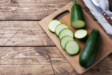 Fresh green zucchini cut into slices on a cutting Board. Wooden rustic table background. Copy space