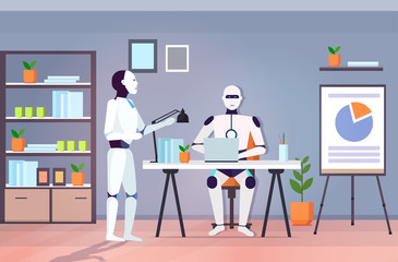Wall Mural - modern robots team using laptop robotic coworkers brainstorming at workplace artificial intelligence technology concept modern office interior horizontal full length vector illustration