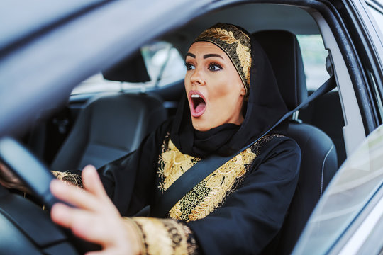 Shocked beautiful muslim woman in traditional wear sitting in her car and just had car accident.