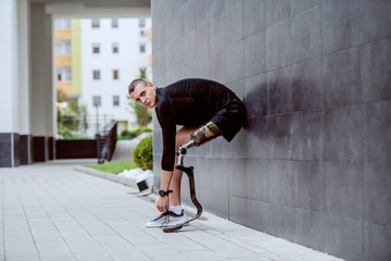 Fotomurales - Side view of attractive caucasian sportsman with artificial leg leaning on the wall and tying his shoelace.