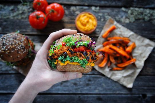 Hand holding vegan sweet potato black bean burger. Plant based food concept