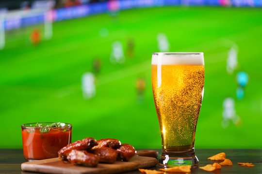 Spicy barbecue chicken wings, tomato salsa, nachos and beer on dark wooden bar table. Football on background, high resolution