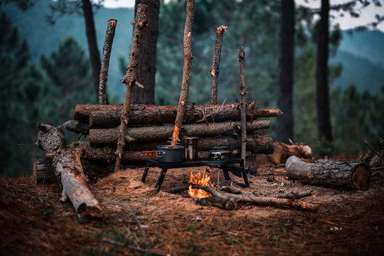 Primitive Bushcraft survival debris hut with campfire ring outside. Blanket, shelter, fire in the forest.