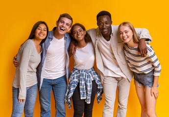 Friendly group of international students smiling over yellow background