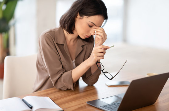 Exhausted manager girl massaging nose and using laptop