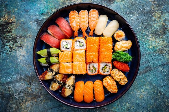 Set of sushi and maki with soy sauce over blue stone background. Top view with copy space