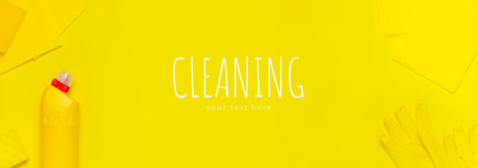 House cleaning concept. Household chemicals, disinfectant, bleach, antibacterial gel, yellow rubber gloves, sponge, rags on yellow background. Flat lay top view copy space. Cleaning accessories