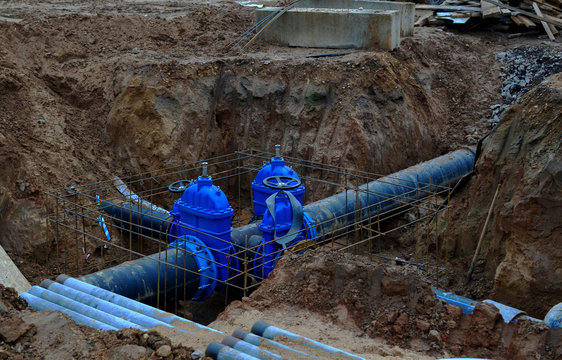 Laying underground storm sewers at construction site, water main, sanitary sewer, drain systems.  Groundwater system for new residential buildings in the city. Ball valve background. Small sharpness