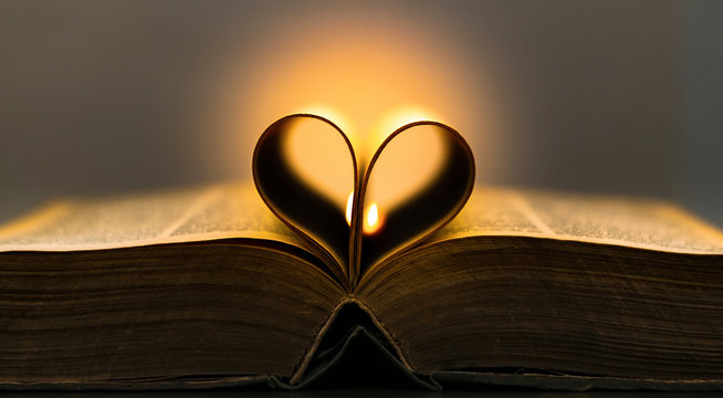Old book pages in a heart shape with a flame in the background