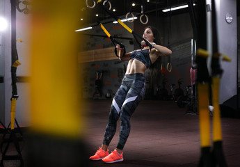 Sport backgrounds. Powerful attractive muscular woman fitness trainer do battle workout with ropes...