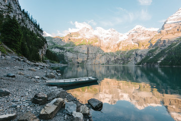 Boat on the shore of Lake Oeschinensee in Switzerland during a dramatic sunset reflection
