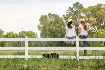 Two western girls sitting on a fence, laughing. Bridger, Montana, USA