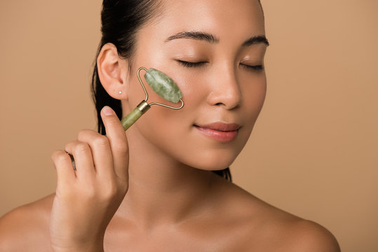 beautiful naked asian girl with closed eyes massaging face with jade roller isolated on beige