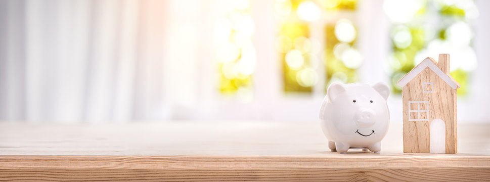 Piggy bank and model house on a bright interior room background