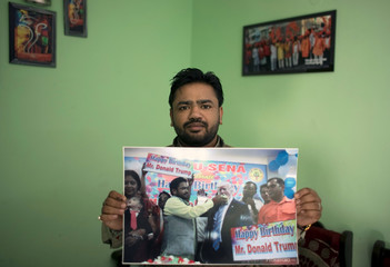 Vishnu Gupta, President of Shiv Sena, a Hindu hardline group, shows a picture of him celebrating US President Donald Trump's birthday, at his residence in New Delhi