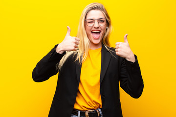 young pretty blonde woman smiling broadly looking happy, positive, confident and successful, with both thumbs up against yellow wall