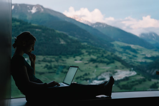 Side view of skilled female digital nomad working remotely on freelance project sitting at table near big window with breathtaking view of high mountains,millennial woman typing content text on laptop