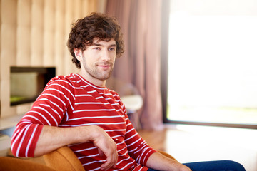 Confident man relaxing at home
