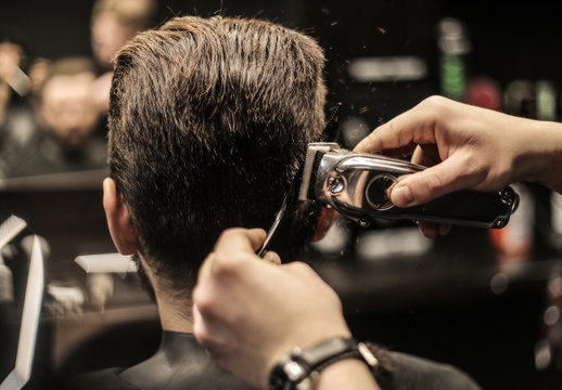 Men style. Close up photo of a barber's hands working with electric shaver and comb to make a new hairstyle for a customer.