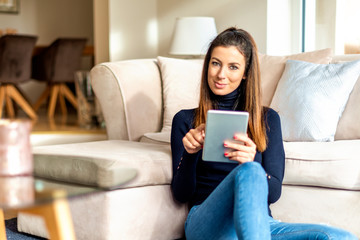 Attractive woman with her touchpad relaxing at home
