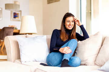 Beautiful smiling woman relaxing on the couch at home