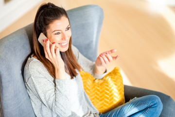 Happy woman making a call while sitting at home