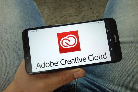 KONSKIE, POLAND - April 13, 2019: Man holding smartphone with Adobe Creative Cloud logo