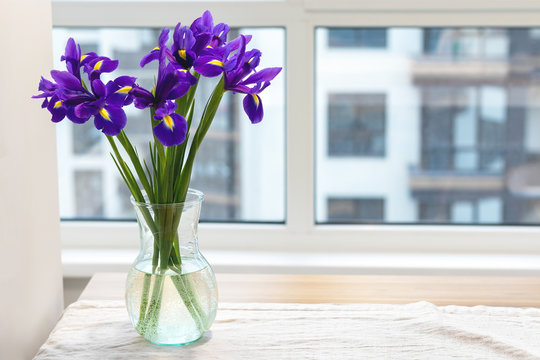 Bouquet of purple irises in a clear glass vase on a linen tablecloth on a wooden table by the window in a modern bright kitchen against a blurred background