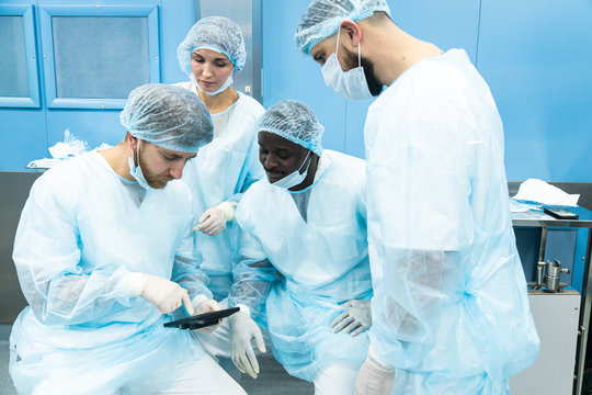 A team of doctors in uniform and medical masks looks at a surgical plan on an electronic tablet