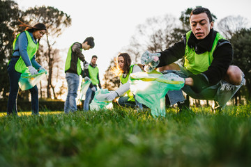 Group of friends during a volunteer garbage collection event in a park at sunset - Millennial having fun together - Happy people cleaning area with bags - Ecology concept