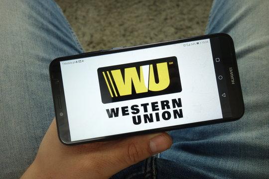 KONSKIE, POLAND - April 13, 2019: Man holding smartphone with Western Union Company logo