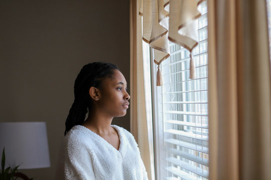 African-American teenaged girl looking out a window and feeling sad and lonely