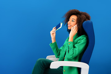 smiling african american woman talking on smartphone and holding passport with air ticket isolated on blue Wall mural