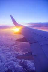 Beautiful sunset, sky on the top view, airplane flying view from inside window and cloud, sun down background aircraft of Traveling.