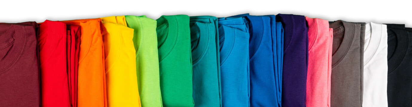 wide panorama row of many fresh new fabric cotton t-shirts in colorful rainbow colors isolated. Pile of various colored shirts white background