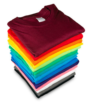 Stack of many fresh new fabric cotton  t-shirts in colorful rainbow colors isolated. Pile of various colored shirts  white background