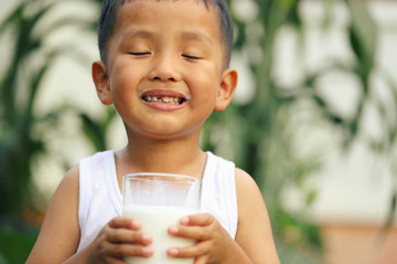 An Asian boy is drinking milk from a large glass.