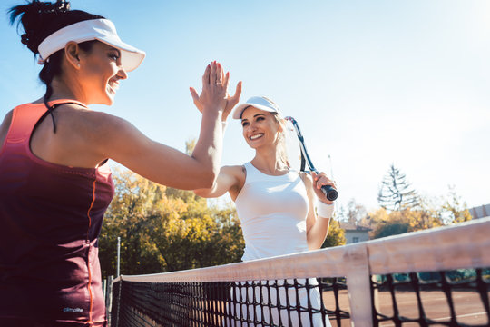 Women giving high five after a good match of tennis